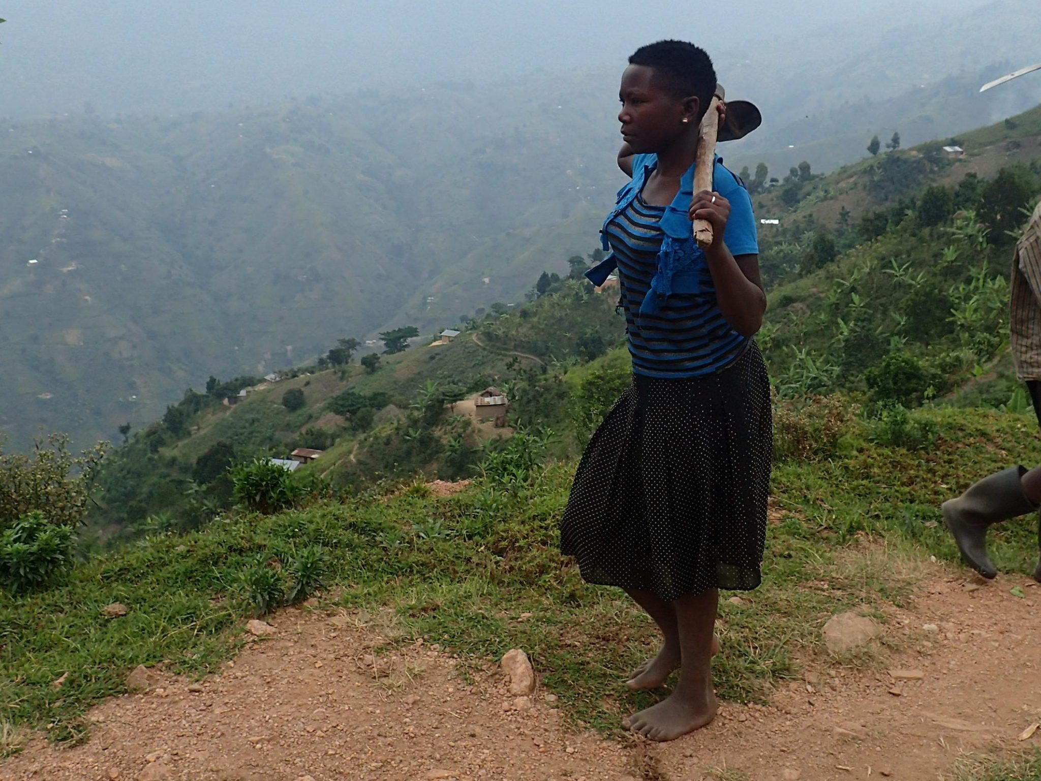 A Kyarumba woman walks home after a day of tending to her crops.